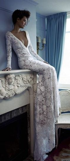 Gorgeous full length white lace gown...just hanging out on the fireplace mantle...that's all.