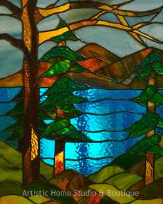 Beautiful stained glass window made by one of our students in our 6-week stained glass class.  Trees, lake & mountains - looks like Lake Tahoe!
