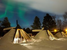 cozy lavvo tent covered in snow with the Northern Lights dancing overhead. This is at the Holmen Husky Lodge in Alta.