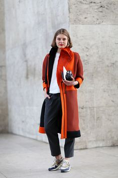 How To Dress Like A French Girl #refinery29  http://www.refinery29.com/63682#slide-4  Sneakers were everywhere in Paris. We love the way they funk up this outfit of staple pieces and a statement coat.