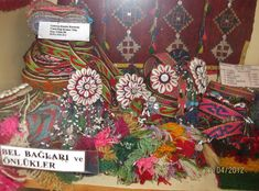 Several 'çarpana bel bağı' (narrow card-woven belt), for women.  From the Edremit district (in the West of the Balıkesir province).  Ethnic group: Tahtacı (Alevi Türkmen).  With a 'göz'-motif (= eye) executed with shells placed around a central button.  The 'göz' is an amulet against the evil eye.   Dated: late 1950s.  On exhibit in the Tahtakuşlar Museum.