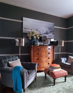 Two Robert Abbey floor lamps flank a William IV bowfront chest from Mrs. MacDougall and create a silvery gleam against dark walls painted in Palais Royal by Ralph Lauren Paint, with Pale Grey on the battens. Bulgari chairs and kilim-covered stool from George Smith. Harnaz cashmere throw. Seneca rug, Thom Filicia Home for Safavieh.