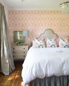 Antonina Vella Dolce Vita Wallpaper covers an accent wall of this colorful orange and gray bedroom boasting a gray French headboard positioned behind a bed dressed in a pleated bedskirt and a white and gray monogrammed duvet topped with colorful Chinoiserie pillows lit by a French chandelier.
