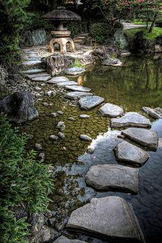 Stepping stones and stone lantern at Kyu-Yasuda gardens in Ryogoku, Tokyo, Japan