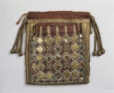 Reliquary bag, Trier, c. 993; Front: Samit, silk, purple, side and bottom yellow, metal flake silver gilt, pearls, Almandine, glass rivers, blue, red, embroidery, metallic threads, recessed landing technique, silk, satin stitch, metal cord, application technique, Metallborte. Back: Samit, silk, silver, metallic thread embroidery, recessed landing technique, contours silk, brown, stem stitch. Silk lining, black, plain weave, silk cord, tassels, metallic thread, silk, wood core, 15cm x 13cm