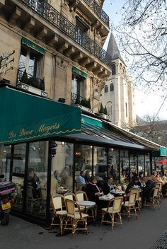 Les Deux Magots  is a famous café in the Saint-Germain-des-Prés area of Paris, France. Its historical reputation is derived from the patronage of Surrealist artists, intellectuals such as Simone de Beauvoir and Jean-Paul Sartre, and young writers, such as Ernest Hemingway. Other patrons included Albert Camus, Pablo Picasso, and the American writer Charles Sutherland.