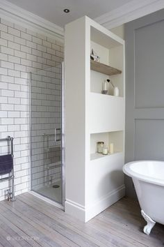 Use the wall that separates the shower to store bathroom items.