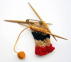 "Brooch ""knitting""  8 CM Long, made in Indonesia between 1942-1945    Wooden Toothpicks and cotton produced brooch depicting a knitting in the colors red, White, blue with an orange ball if breiknotje. On the back is a pin confirmed. Such brooches with veiled references to the Netherlands and the orange house were many made as a sign of resistance in the quiet vrouwenkampen. Dutch Knits, 1635-1969 by Constance Willems at www.knitdesign.com Orange House, Knitting Needles, Red Color, Knits, Brooches, Netherlands, Dutch, Sign, Colors"