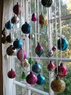 Holiday Window ~ ornaments hanging from ribbon. My friend's family did this in the hallway each year. They hung the ornaments from clear fishing wire at varying heights. There was a large mirror at the end of the hall that reflected all the balls, it was very beautiful.