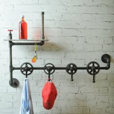 Our Industrial Vintage Bicycle Parts Coat Hook Rack is a unique and quirky storage solution. Constructed from recycled bicycle parts and gas pipes, this is upcycling at its best! With a clever use of steel pipes and bicycle gears, these random scrap parts are transformed into coat hooks and shelf racks. Featuring a reclaimed wood shelf and four coat hooks. Perfect as a statement piece for your hallway or open living space.  MetalW 107 x H 76 D 19cm