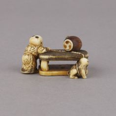 3)An ivory netsuke, unsigned, of a child and a cat at a table, the cat tied with a length of rope, the child holding the other end, a barrel on the table. Condition…perfect