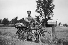 1915: Rural Delivery A mail carrier stands with his Wagner 4-11 motorcycle next to a postal box along his route near Newell, South Dakota. The mail is in the sacks on the rear of his motorcycle.