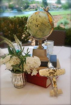 cute centerpiece with books, globes, and planes / http://www.deerpearlflowers.com/travel-themed-wedding-ideas-youll-want-to-steal/