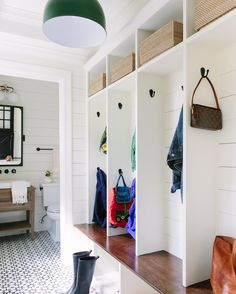 LOVE this mudroom. Lockers with mattle black side hooks (lower ones for the kiddos) wooden seat. Open space on top and below. Fantastic statment tile, shiplap, GREEN industrial pendant.