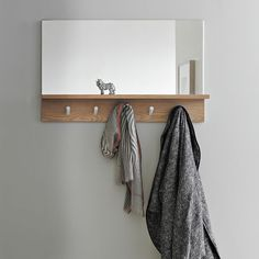 "West Elm | Exit strategy. This simple entryway mirror features a shallow shelf to store keys, pegs to hang coats and a mirror to consult on the way out the door. An all-in-one system that's great for small spaces. • Mirror; engineered wood with barley-stained finish. • 34""w x 21.5""d x 5.75""h. $199"