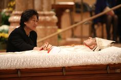 A mourner touches the hand of Cardinal Francis George before the funeral Mass on Thursday, April 23, 2015 in Chicago.  George died last Friday at age 78 after a long battle with cancer.
