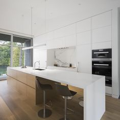 The kitchen is open and white, in accordance with the rest of the living spaces and has this stylish island-bar