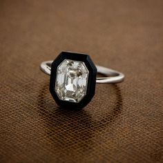 A beautiful and rare antique engagement ring. An emerald cut diamond surrounded by a halo of onyx and set in platinum. Circa 1920