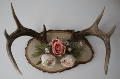 Large deer antlers, mounted and then decorated with artificial flowers.