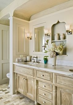 example of a lighter finish cabinetry, subway stone floors, marble top, sconce lighting, etc.