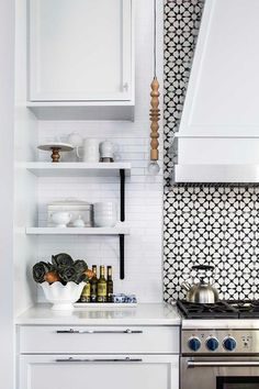 Gorgeous black and white mosaic cooktop tiles are positioned behind a white wood clad hood mounted above a stainless steel oven range. design behind stove Contemporary Style Kitchen, Home Decor Kitchen, Kitchen Remodel, Contemporary Kitchen, White Kitchen Tiles, Kitchen Remodeling Projects, Black And White Backsplash, Home Kitchens, Kitchen Design