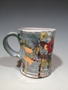 This is an earthenware mug glazed with a white glaze over a glossy green glaze. This cup was wheel thrown and after being glaze fired I applied laser toner transfers over vintage flower decals. I then refired it with red poppy decals, and gold luster decals. Justin Rothshank  This mug is decorated with gold luster decals. For this reason it cannot go in the microwave, but it can go in the dishwasher.