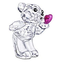Kris Bear - Blowing Kisses                Show your affection for a loved one with this cute little Kris Bear. He shows emotions and detailed facial expressions. The fully faceted clear crystal figurine is holding an unfaceted Fuchsia crystal heart. His innocent eyes and tiny nose shine in Jet crystal. A printed mouth is blowing the heart away like a kiss.