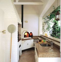 Para ter um espaço de lazer abrigado por um terraço, os arquitetos Sandra Ruiz e Shintaro Arakawa construíram uma estrutura de madeira coberta por telhas de ardósia. Tijolos refratários pintados de branco revestem a churrasqueira e o forno de pizza. Para servir de apoio às refeições, foi construído um balcão de alvenaria com tampo de granito amêndoa.