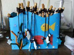 We gaan vissen. Beplak een doos met blauw karton met aan de bovenzijde golfjes geknipt. Als versiering knip je uit andere kleurtjes karton wat visjes en wier. Als luchtbelletjes kan je plakkraaltjes of glitters gebruiken. (o.a. verkrijgbaar bij de action) In de doos staan soepstengels als hengel en dropveters als visdraad. Het visje kan je bv kopen bij de snoepkraam op de markt