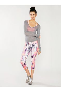 A light pink sports bra, a gray wide v-neck open-knit sweater, light pink tie-dye cropped leggings, and silver running shoes. A school or workout outfit for spring or fall.