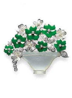 A JADEITE, DIAMOND AND FROSTED GLASS BROOCH  Designed as a vase of flowers, comprising six translucent rich green jadeite flowerheads with diamond collet inset, enhanced by circular-cut diamond flowers and leaves, to the frosted glass vase with ropetwist detail, mounted in 18k white gold, brooch 4.7 cm. wide, largest jadeite flowerhead approximately 11.52 x 0.80 mm.