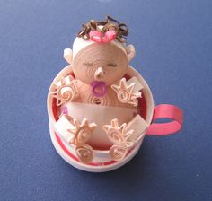 "Baby in a teacup.  Height is 1 1/4"".  All out of quilling paper. Made for my daughter at the birth of her daughter. Cathy Schlim."