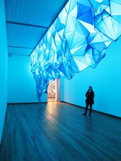 """""""What Lies Beneath"""" by Gabby O'Connor is an unexpected and original art installation. A place specific glowing iceberg entirely made of paper tissue and inspired of Antarctica's iceberg forms. """"What Lies Beneath"""" was firstly installed at Wellington City Gallery (NZ) in 2011. The room had a skylight and the dimensions of the installation matched exactly the opening of the skylight. Fluorescent lamps were also used in combination to the natural light coming from the ceiling, to provide an even…"""