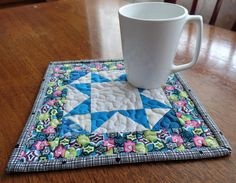 This patchwork star mug rug will brighten up your coffee or tea time, perfect for your table or desktop! Or, it might be just the right gift for a coworker, friend, or family member. Think of how much better your drink will taste with this great mug rug underneath it! Details: - measures 8.5x 8.5 - is made of multiple cotton fabric scraps and back is a solid Kona blue. -meander quilting is stitched with Perma Core polyester thread. -batting is Hobbs 80/20 (80% cotton and 20% polyester) ... Etsy Quilts, Lap Quilts, Mug Rugs, Potholders, Quilt Bedding, Gifts For Coworkers, Tea Mugs, Fabric Scraps, Table Runners