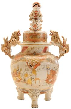 A gilt decorated Satsuma pottery covered censer, the cover with seated foo lion finial, gilt border surround, body with applied foo lion handles, alternating figural and floral decoration, animal paw feet. Circa 1801-1900