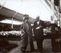 Vorstenhuizen, koningshuis Nederland. Officiële bezoeken van Wilhelmina.  Wilhelmina bezoekt in lang gewaad en met een tulband-hoofddeksel de  bloemententoonstelling in Boskoop. De voorzitter van het tentoonstellingsbestuur  begeleid haar. Boskoop, Nederland, 1911.