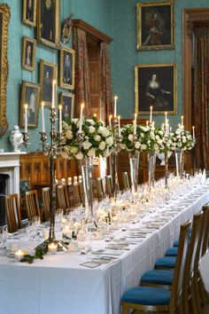 Wedding reception long dining table white roses and green tall vase arrangements, candelabras and floating candles Cherie Kelly Knowsley Hall