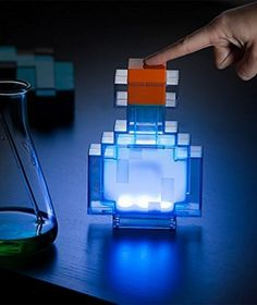"""""""Bring the magic of brewing in Minecraft to the real world with this Minecraft Potion Bottle. This little shatter-resistant bottle looks like it came right out of the game and lights up 8 different colors: indigo, light blue, cyan, green, peach, yellow, red, and white. With a tap, it moves between colors. Place it anywhere – it runs on 2 AAA batteries – and let it help you keep the hostile mobs away. #minecraft #toy #gadget"""