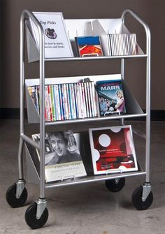 This double-sided steel cart features sloping top shelves for face-out book display and shallow bins beneath for all of the accessories.