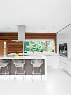 Bertoia bar stools by Knoll are tucked under the island in the Scavolini Scenery kitchen. Jordan replaced the original wood flooring with white resin, a robust surface used in high-traffic environments. Photo by Jon Snyder.