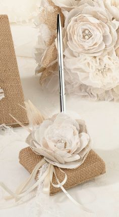 Wedding Pen Burlap and Lace Country chic wedding pen set features a silver pen rests upon a burlap covered base. The base combines a flower with rhinestone ornament in the center, a natural peacock feather, lace and ribbon.