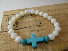 Pulseira MOESI Peace feita em fio de silicone com madrepérolas e detalhe cruz em turquesa. #pulseira-moesi-peace