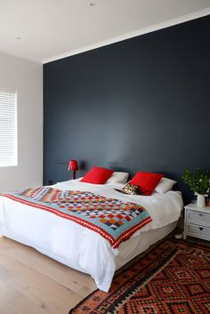 Master bedroom with dark accent wall. The quilt is vintage and the bedside tables are hand-me-downs.