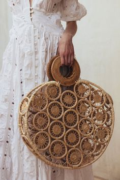 An updated take on the classic straw bag featuring our classic Rattan circular handle.