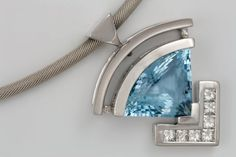 Solid 18 carat white gold pendant featuring a 7.70 carats trillion cut Aquamarine in a half-bezel setting and 7 princess cut Diamonds G in colour VVS in clarity, totaling in weight 0.65 carats in a channel setting.   By:  Aharoni Jewellery