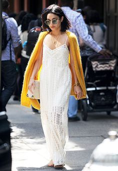 Vanessa Hudgens in a yellow cardigan, white dress,  white bag, sunglasses, and sandals