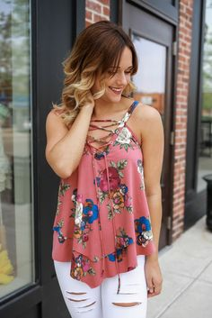 If you're jetting off the the Tropics this Summer, don't forget to pack this little number! It is a festive sleeveless, layered trapeze tank with a lace up neckline, asymmetrical hemline, and floral p