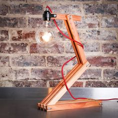 This classic and unique light is made from 9 strips of beautiful recycled Saligna wood, with an exposed large LED filament style bulb, just to show off a little, and  to give off maximum light.Size: LargeHeight: approx. 57 cmLight bulb: Large Filament style 5w warm white LEDCable length: 2 meter red fabric cable Desk Lamp, Table Lamp, Unique Lighting, Red Fabric, Light Bulb, Recycling, Cable, Artisan, Led