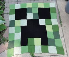 """Knit this Creeper blanket for yourself or any Minecraft fan. The knitted 8"""" garter squares form this pixelated afghan."""