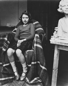 U.K. Photograph of Princess Elizabeth at Professor de Strobl's studio, seated on a chair covered with a tartan blanket, next to a larger-than-life size marble sculpture portrait of herself. circa 1935.